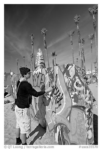 Young man making graffiti on a wall. Venice, Los Angeles, California, USA (black and white)
