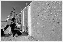 Young men creating graffiti art on a wall on the beach. Venice, Los Angeles, California, USA ( black and white)
