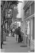 People looking at store display on Main Street. Half Moon Bay, California, USA (black and white)