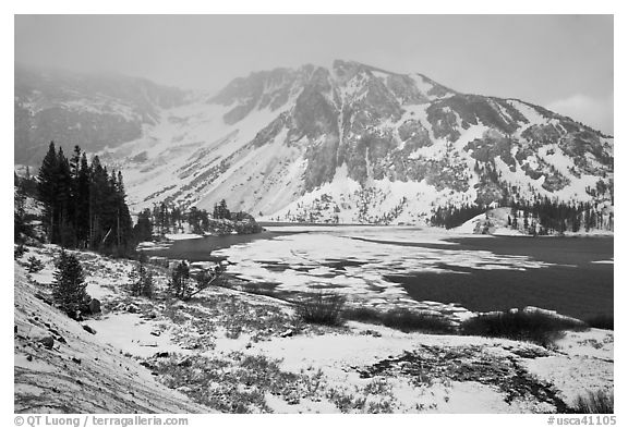 Partly frozen Ellery Lake and mountains with snow. California, USA (black and white)