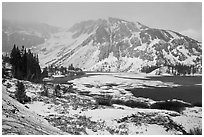 Partly frozen Ellery Lake and mountains with snow. California, USA ( black and white)