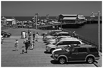 People drapped with colorful towels walking on wharf. Santa Barbara, California, USA (black and white)