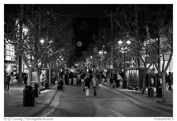 Couple walking on pedestrian Third Street by night. Santa Monica, Los Angeles, California, USA (black and white)