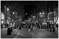 Couple walking on pedestrian Third Street by night. Santa Monica, Los Angeles, California, USA ( black and white)