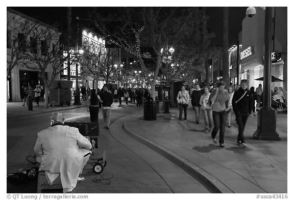 People walking past mime on Third Street Promenade. Santa Monica, Los Angeles, California, USA (black and white)
