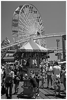 Families, amusement park and ferris wheel. Santa Monica, Los Angeles, California, USA ( black and white)