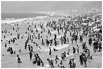 Crowds of beachgoers in water. Santa Monica, Los Angeles, California, USA ( black and white)