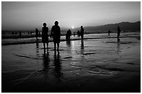 People and reflections on beach at sunset, Santa Monica Beach. Santa Monica, Los Angeles, California, USA ( black and white)