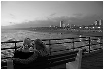Two women sitting on bench at sunset , Santa Monica Pier. Santa Monica, Los Angeles, California, USA ( black and white)