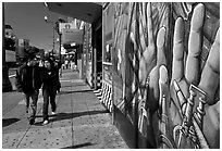 Couple walks past mural on Mission street, Mission District. San Francisco, California, USA ( black and white)