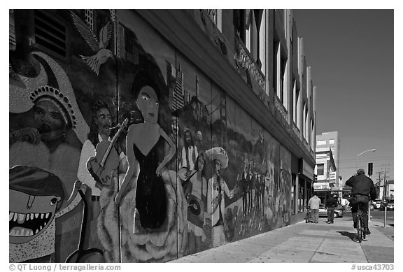 Man riding bicycle on sidewalk past mural, Mission District. San Francisco, California, USA (black and white)