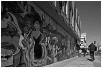 Man riding bicycle on sidewalk past mural, Mission District. San Francisco, California, USA ( black and white)