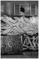 Mural paintings below broken window, Mission District. San Francisco, California, USA ( black and white)