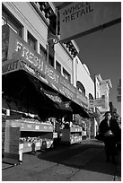 Woman walks past vegetable store, Mission Street, Mission District. San Francisco, California, USA (black and white)