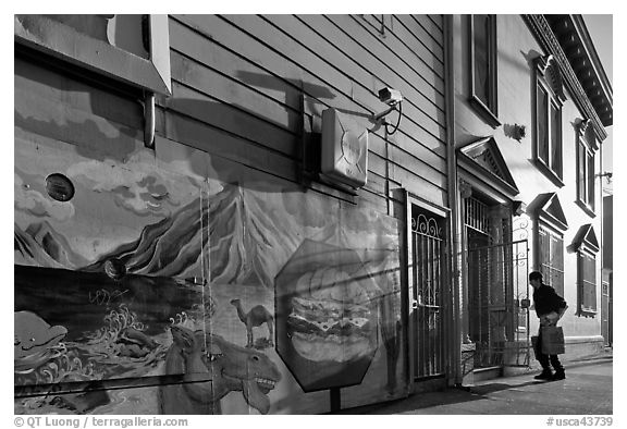 Mural and man entering house with grocery bags, Mission District. San Francisco, California, USA (black and white)