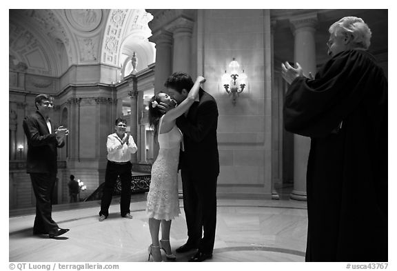 Just married couple kissing, witness and officiant applauding, City Hall. San Francisco, California, USA (black and white)
