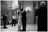 Just married couple kissing, witness and officiant applauding, City Hall. San Francisco, California, USA ( black and white)