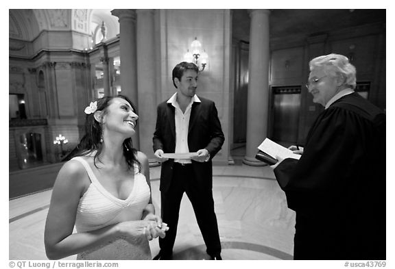 Bride and groom exchange smile with wedding official, City Hall. San Francisco, California, USA (black and white)