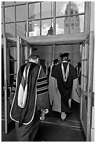 Professors in academic regalia walk into door with Hoover tower reflected. Stanford University, California, USA ( black and white)