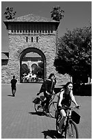 Students riding bicycles through Main Quad. Stanford University, California, USA (black and white)
