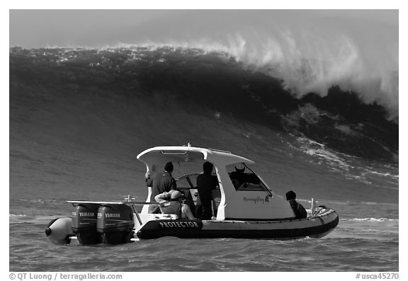 Small boat dwarfed by huge wave. Half Moon Bay, California, USA (black and white)