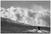 Jet ski dwarfed by huge breaking wave. Half Moon Bay, California, USA ( black and white)