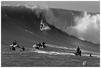 Surfer down huge wall of water observed from jet skis. Half Moon Bay, California, USA (black and white)