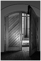 Wooden door opening to wine storage tanks. Napa Valley, California, USA (black and white)