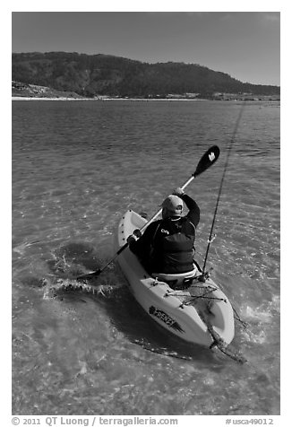 Sea kayaker with fishing rod in Carmel Bay. Carmel-by-the-Sea, California, USA (black and white)