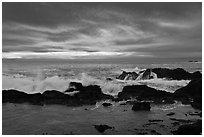Wave crashing on rock at sunset. Point Lobos State Preserve, California, USA (black and white)