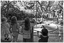 Children watching animal exhibit, Happy Hollow Zoo. San Jose, California, USA ( black and white)