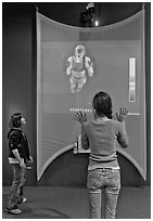 Girls play with thermal imaging camera, Tech Museum. San Jose, California, USA (black and white)
