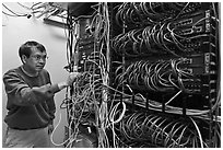 Technician rearranging data cables. Menlo Park,  California, USA ( black and white)