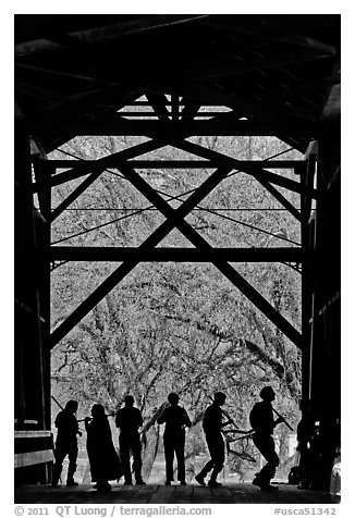Silhouettes of people dancing inside covered bridge, Felton. California, USA (black and white)