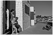 Family steps out of colorful cottage. Capitola, California, USA (black and white)