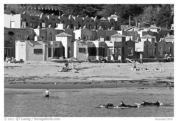Surfers, beach, and Venetian hotel cottages. Capitola, California, USA (black and white)