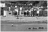 Surfers, beach, and Venetian hotel cottages. Capitola, California, USA ( black and white)