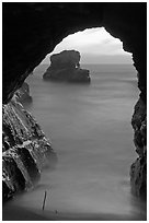 Ocean seen from sea arch at sunset, Davenport. California, USA (black and white)