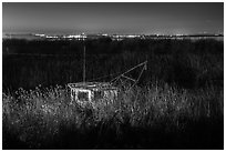Fishing boat amongst tall grasses by night, Alviso. San Jose, California, USA (black and white)