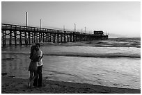 Couple embracing in front of Newport Pier. Newport Beach, Orange County, California, USA ( black and white)