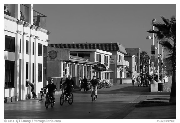 Riding bicycles on beachfront promenade, Hermosa Beach. Los Angeles, California, USA (black and white)