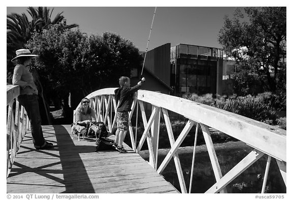 Boy fishing from arched bridge, Venice Canal Historic District. Venice, Los Angeles, California, USA (black and white)