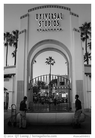Men roll red carpet in front of Universal Studios gate. Universal City, Los Angeles, California, USA (black and white)