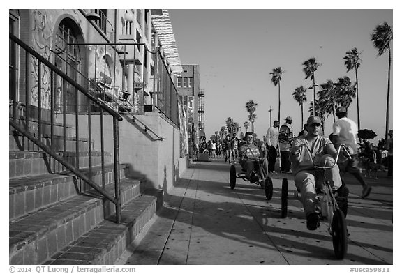 Men riding tricycles on Ocean Front Walk. Venice, Los Angeles, California, USA (black and white)