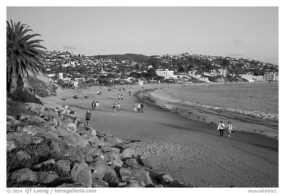 Beach with people strolling in late afternoon. Laguna Beach, Orange County, California, USA (black and white)