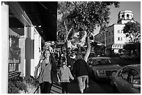 Visitors walk on sidewalk in shopping area. Laguna Beach, Orange County, California, USA ( black and white)
