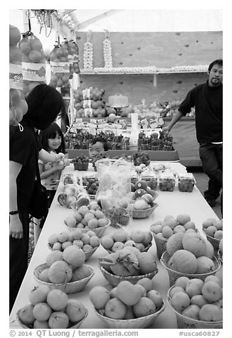 Customers buying fruit at stand. California, USA (black and white)