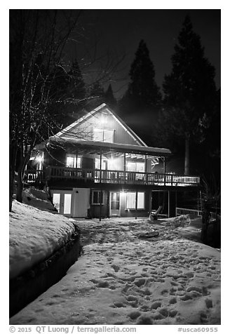 Cabin with window lights in winter. California, USA (black and white)