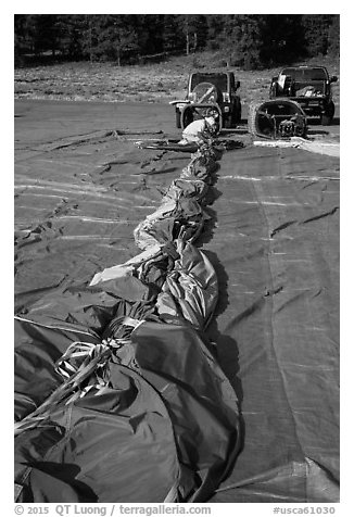 Hot air balloon being folded for transportation, Tahoe National Forest. California, USA (black and white)