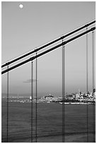 The city seen through the cables of the Golden Gate bridge, sunset. San Francisco, California, USA (black and white)